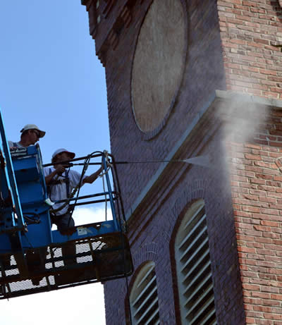 On the tower's west side, two men are in the power lift's platform. One works the controls to reposition the platform; the other directs the power washer wand. The high-pressure spray is removing the years of grime from the brick.