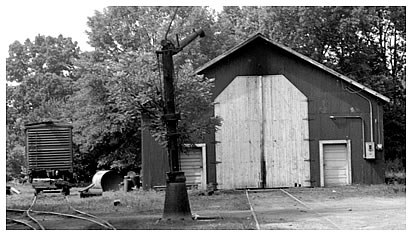The exterior of the engine shed with the tall doors closed. An idle boxcar sits on the siding alongside the shed.