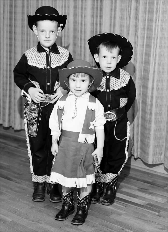 Two small boys, perhaps six and four, and their little sister. All are wearing their cowboy garb that Santa recently brought. The sweet little girl, holding a six-gun in each hand, looking for all the world like Dale Evans, is thrilled to be involved in the photo shoot.