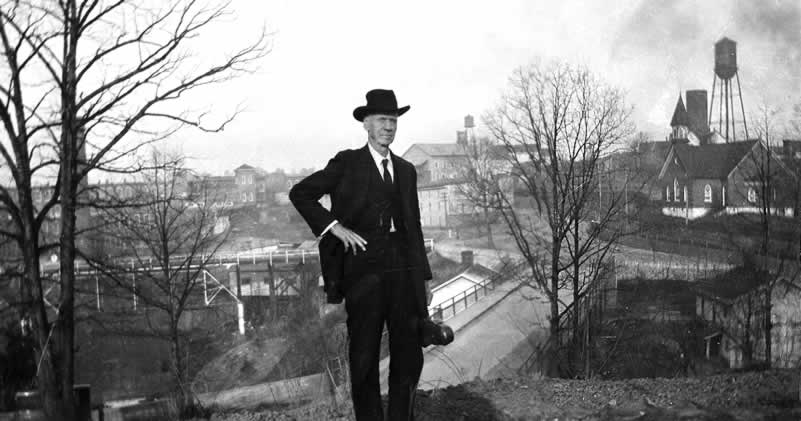 "An elderly gentlemen in black, holding a violin case, stand atop and at the crest of a Cliffside bluff known as ""Highland."" Below  and behind him is an easterly view of Cliffside's two bridges, the Methodist church and other structures."