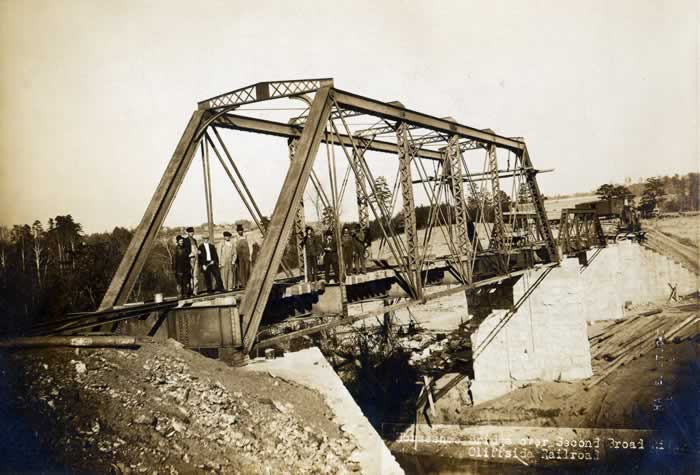 The nearly-finished trestle crossing the Second Broad River near Henrietta. A group of workmen stand on the near end  of the structure.