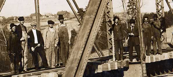 Nine workman are lined up on the trestle.