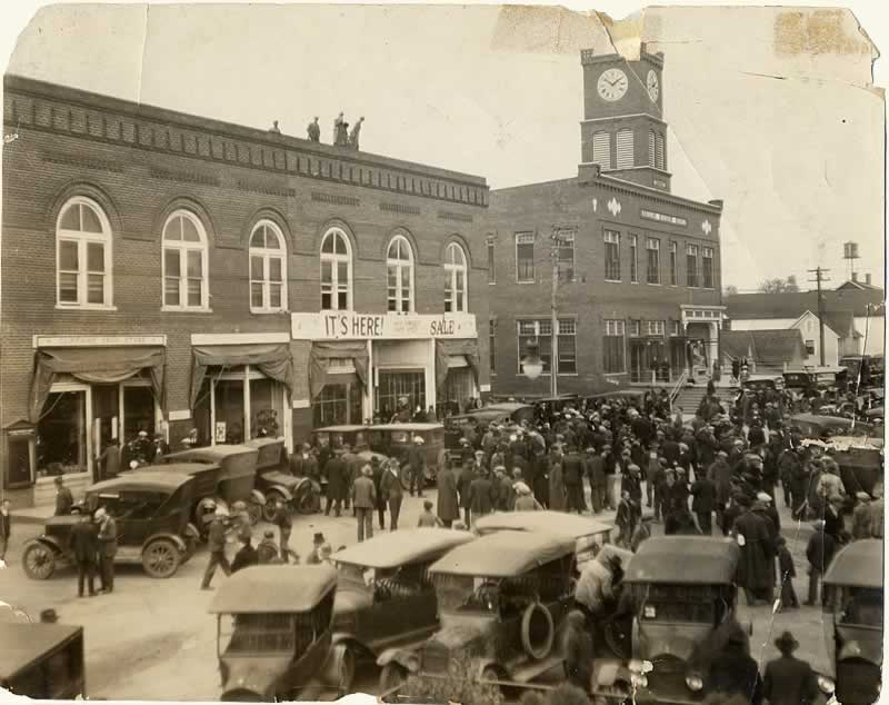 The square is filled with Model Ts and perhaps 200 people milling about in front of the company store building.