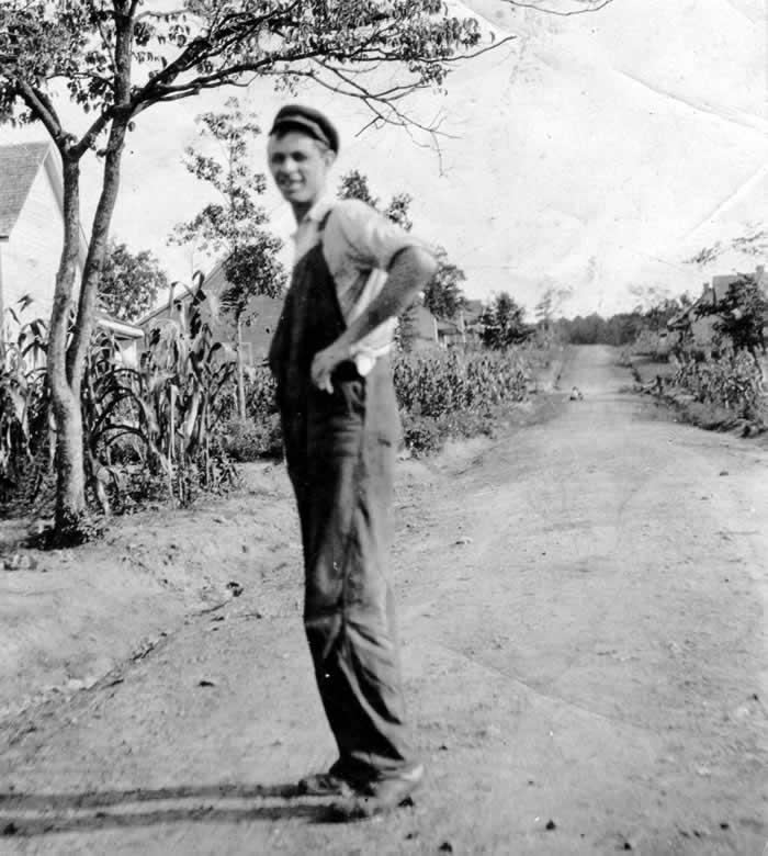 The man, in overalls and short-sleeved shirt, stands smiling at the camera,  near a spindly tree on an unpaved, dirt Cliffside street. All along the street we can see patches of tasseled corn growing in yards.