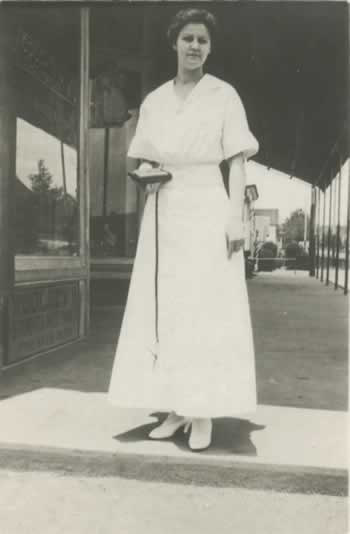 The elegant lady in a white, ankle-length dress and white shoes, pauses at then end of the sidewalk in front of the store.