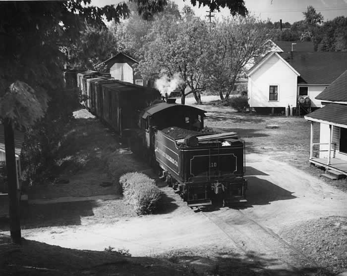 Cliffside engine pulling a train of boxcars through a nest of mill houses situate just yards from the track.