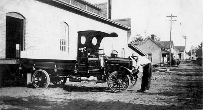 An old-timey pickup truck is backed up to the ice plant loading dock. It's driver is in front of the vehicle. Mill houses can be seen in the distance.