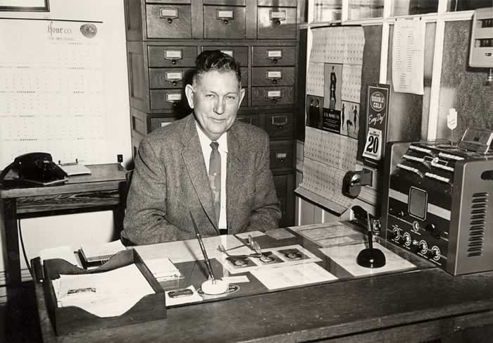 Principal H. C. Beatty at his desk in his office in Cliffside School. A big clunky intercom system sits on the end of his desk. Behind him is a wooden file cabinet with about a dozen drawers of various sizes, which probably has been there since the 1920s.