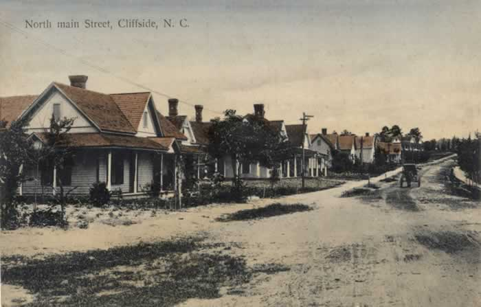 An old postcard showing houses along the unpaved North Main Street in Cliffside. A buggy in the distance is moving up the road.