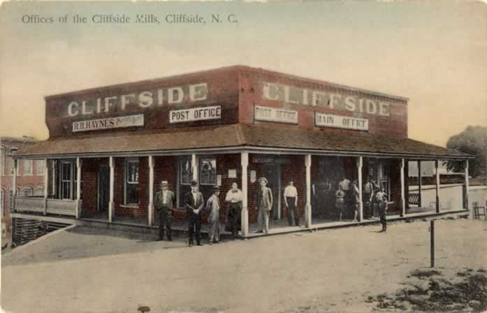 """A two-story red brick building: Cliffside's """"mill office,"""" with big bold signs reading """"CLIFFSIDE,"""" """"R.R. Haynes, proprietor,""""  """"Post Office"""" and """"Train Office"""""""