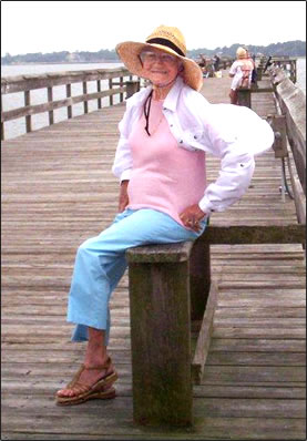 Wearing a wide-brimmed straw hat, a happy Ottie sits on a bench on a long, wooden fishing pier.