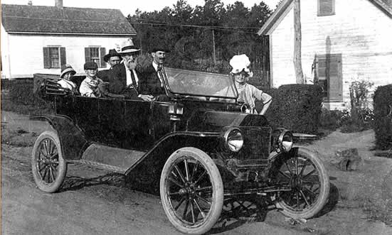 The Watkins family about to drive away in a convertible Ford Model-T touring car. The top is down, the windshied is folded down and they're ready for a drive.
