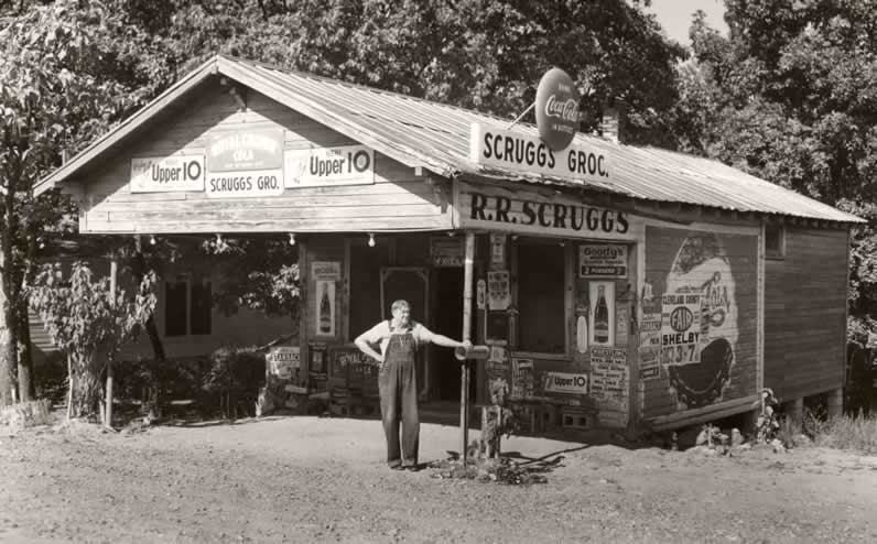The proprietor, dressed in bib overalls, stands in front of his old store, surveying his domain. Although there is no porch, an overhang protects those who might want to sit and whittle, or smoke, or enjoy a cold drink on the benches and boxes on the paved area beneath. The yard is raw dirt and the store's sides and front display tattered advertisements.