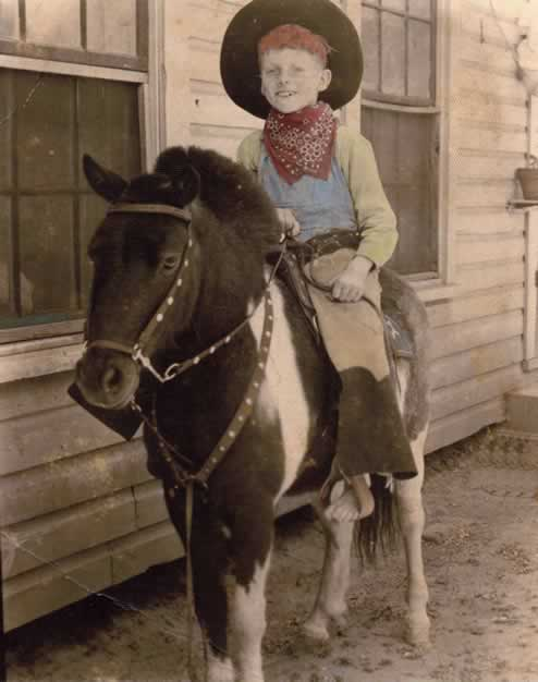 The 'pony' man took this photo with Red mounted on a brown and white semi-steed. He's in the outfit the photographer provides for the picture: leather chaps, red bandana and a cowboy hat. These photos were always posed with the pony standing along-side your house, to catch you (on one side, at least) in case you fell.