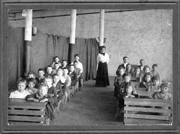 There are two rows, front to back, of eight rough, home-made desks with an aisle running down the center. Two students are seated at each desk. School teacher strands in rear wearing dark floor-length skirt and prim white blouse.