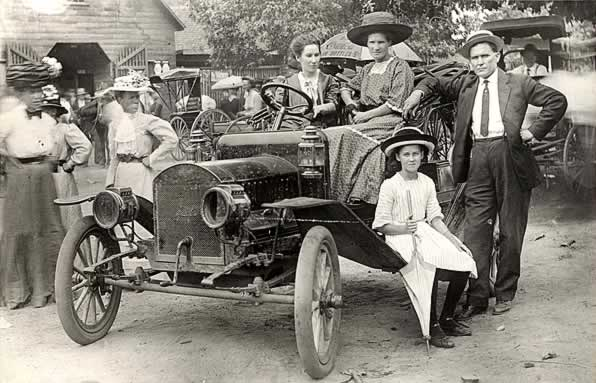 A family group in and around an open car of 1910 vintage, in a gathering outside a livery stable.