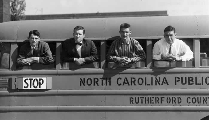 A parked Rutherford County school bus. Four high school seniors, each one with his arms and upper torso sticking through a window.