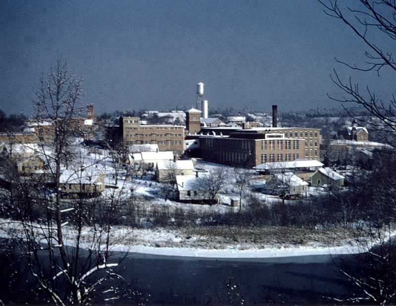 A stunning photo of the south end of town, with the curve of the river in the foreground. The snow-covered houses of South Main fill the area on the far bank. Then the imposing buildings of the mill dominate the scene.