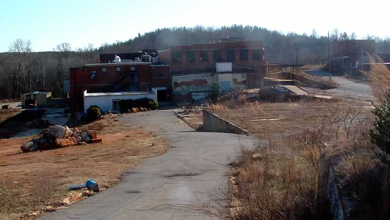 A photo taken decades later. The foreground buildings have vanished, leaving only empty ground and a narrow paved access road. A quarter-mile in the distance is the now unused building that once was used as the packing and shipping department of mill.