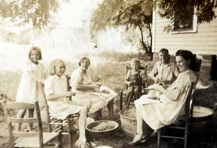 Two mother's and their children sit outdoors in wooden chairs around wash tubs and pans of beans.
