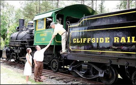 Man on locomotive leans down to shake hands with man on ground.