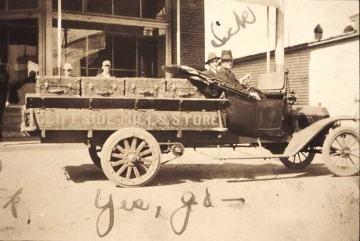 A late 1900's Ford truck in the style of today's pickups stands in front of the store building.