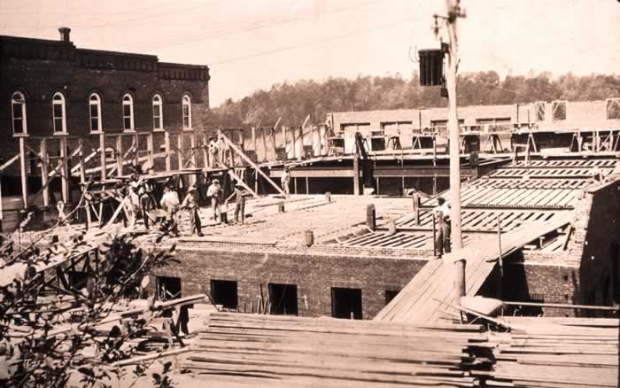 A rare photo of construction underway of the Memorial Building. It has been built up to street level, and workmen are seen laying the floor of what will be the library. On the right, planking for the theater's sloping floor has been installed.