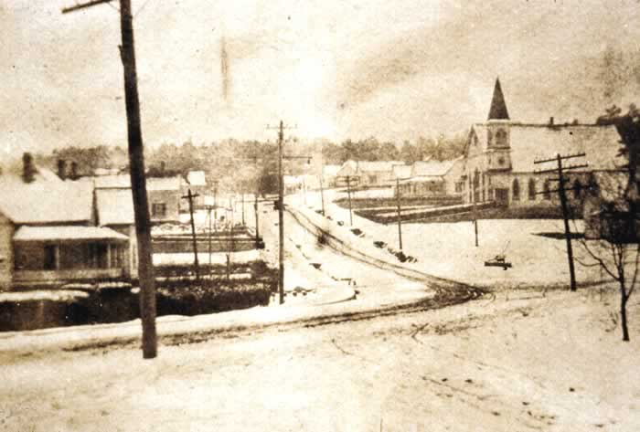Looking up North Main Street on a snowy day. On the right is the old Baptist church.