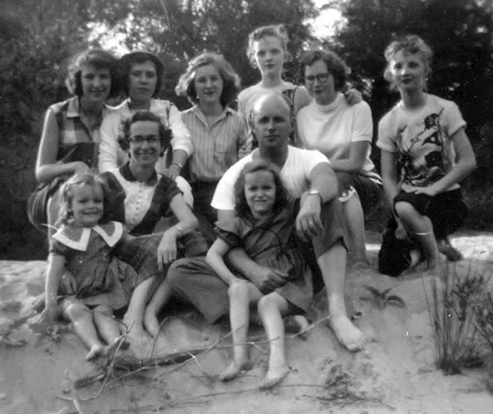 The barefoot Mayse family and school girls sit on a sandy bank of Broad River