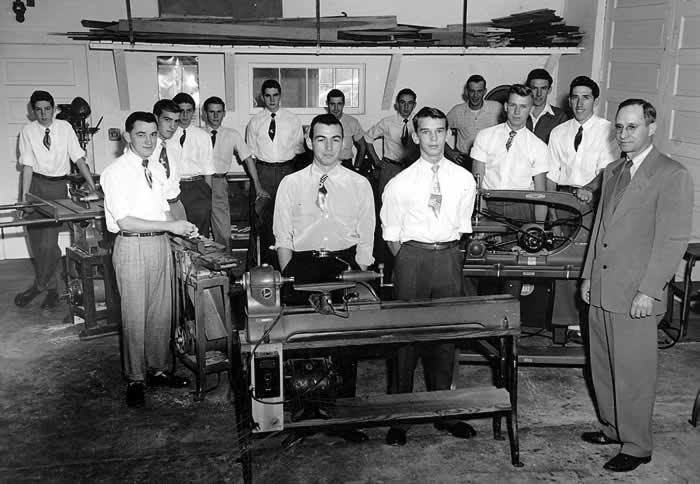 Obviously it's picture day for the yearbook, for all the boys (14 of them) are wearing ties--although tucked neatly into their white dress shirts. They're posed behind various floor-mounted woodworking tools. The instructor, Mr. Frye, stands by solemly in suit and tie.