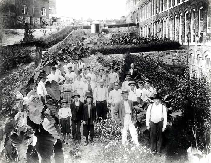 A couple dozen workers, old and young, pose in a massive plot of flowers and greenery alongside the mill.
