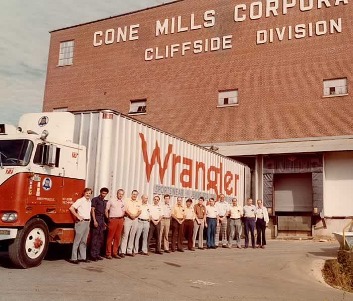 """Outside the Cone Mill Cliffside plant. An 18-wheeler with the word """"Wrangler"""" painted on the side of the trailer. Beside it stand a line of 15 managers of various mill departments."""
