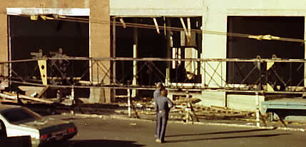 A zoom-in shows the building's interior has been gutted. Scraps of the remains lie about along the front.