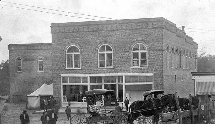 The building sits on a dirt street. A couple of horses (with buggies attached) are tied up to a hitching post. Several men are standing around, in the street and on the sidewalk, as if waiting for something to happen. Nothing likely will.
