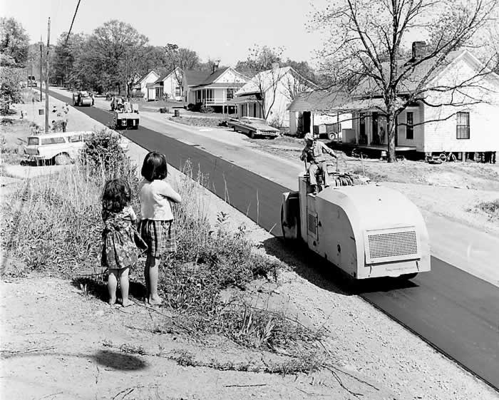 Two little girls standing safely on a rise as rollers pack asphalt on one lane of Cliffside Street.