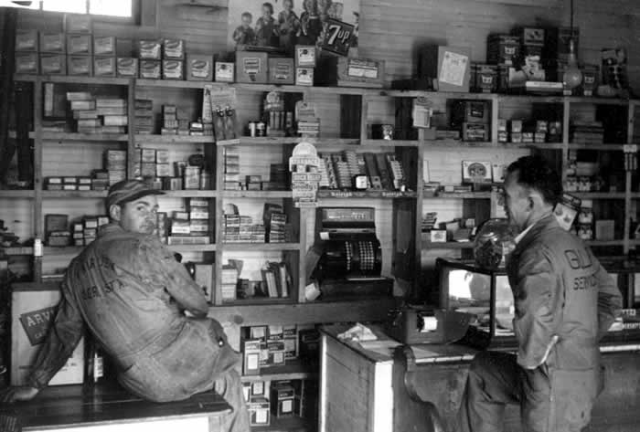 "The interior of a 1950's gas station ""store"" with shelves on the back wall with items for sale: cigarettes, spark plugs, cigars, etc. Two attendants are present, in greasy coveralls."