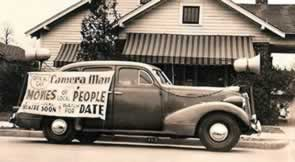 "Car with large banner on side reading ""Camer Man. Movies of our People. Coming to Your Theatre Soon. Watch For Date."""