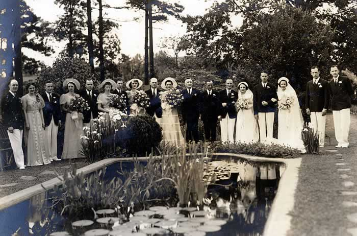 A wedding party of 18 form a line around a goldfish pond. The men are in dark coats and white pants; the ladies are in long gowns. The brides are in their wedding ensembles. The fishpond contains lilypads and other plants.